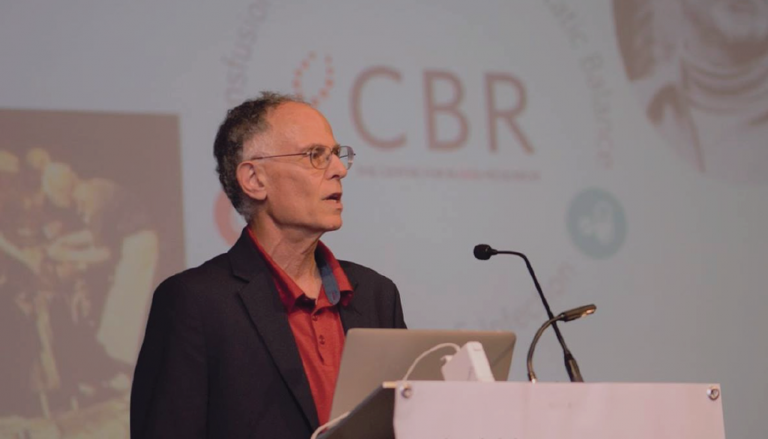 Dr. Ed Conway standing at a podium in formal attire; the CBR logo is visible in the background
