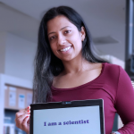 """Sree smiling at the camera and holding up a tablet with both hands with the words """"I am a scientist"""" written across the screen in fun-looking, purple font. She seems to be standing in a lab space or office space."""