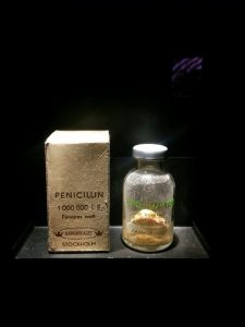 A glass bottle of penicillin, which looks like a gold substance, next to a box for the medication. Both appear to be in a display case under bright lighting.